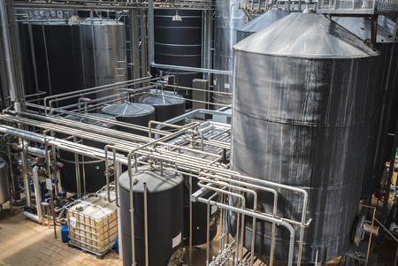 microbrewery: Row of stainless tanks in microbrewery. Modern interior.