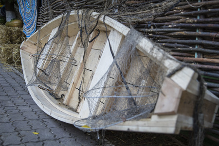 upturned: Wooden fishing boat with chain lies near a wicker fence