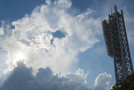 Stadium lighting tower and stormy cloudy sky