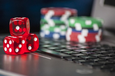 gambling counter: Gambling chips, red dice on laptop keyboard background Stock Photo