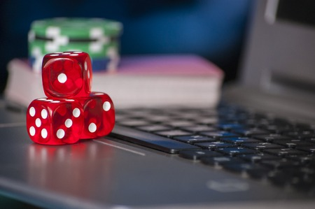 Gambling chips, red dice on laptop keyboard background Stock Photo
