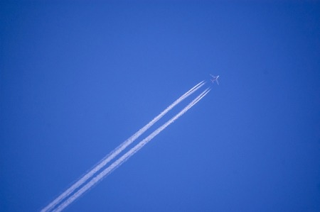 A plane flying on a perfectly blue sky with vapor trail Imagens
