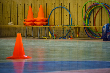 Interior of a gym at school, red cones on a row