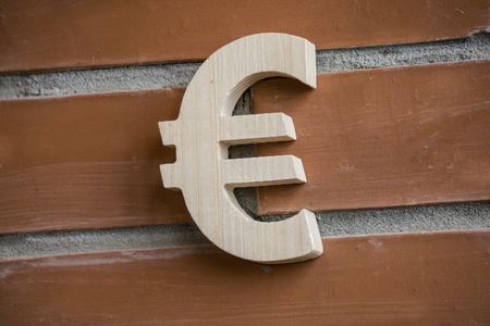 Wooden euro symbol on brick wall background