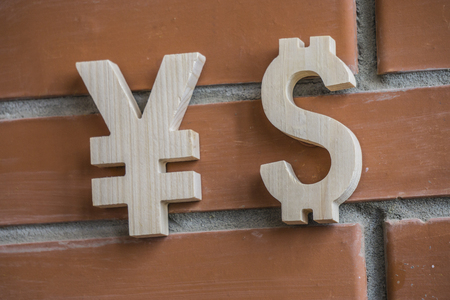 Exchange rate. Wooden yuan or yen and dollar symbol on brick wall background Zdjęcie Seryjne