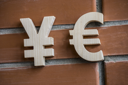 Exchange rate. Wooden yuan or yen and euro symbol on brick wall background
