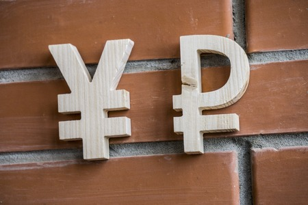 Exchange rate. Wooden yuan or yen and broken ruble symbol on brick wall background Zdjęcie Seryjne
