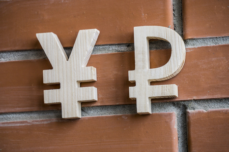 Exchange rate. Wooden yuan or yen and ruble symbol on brick wall background Zdjęcie Seryjne