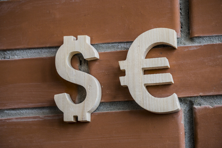 Exchange rate. Wooden dollar and euro symbol on brick wall background