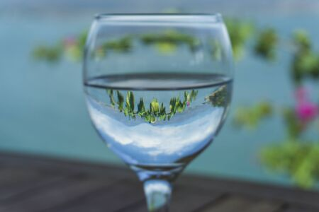 Glass of water with closeup on ocean and mountain nature blur background Zdjęcie Seryjne