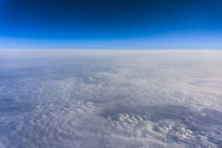 Above clouds, view from pilot cabine airplane. Blue sky, white clouds with magic and soft sun light. Zdjęcie Seryjne