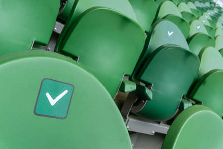Empty plastic seats in a stadium. Stickers intended to promote social distancing in the arena.