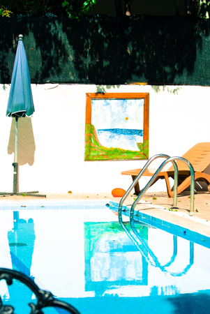 loungers: Pool with sun lounger and parasol. Retro style. On the wall hangs a painting. Summer dresses
