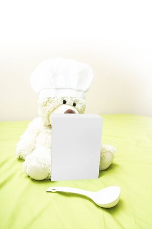 baby bear: Teddy bear in a chefs hat touting a box of baby food. Teddy bear sitting next to a box of childrens gruel and spoon. The concept of advertising for baby nutrition. Blank packaging paper box. Stock Photo