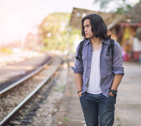 Long haired man that looks cool He is a traveler or nomadic musician who is backpacking and guitars, walking near train track in rural.