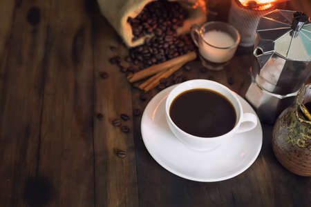 a cup of coffee americano placed on wooden table, There are stove, roasted coffee beans sag and Italian coffee maker(mocha pot)