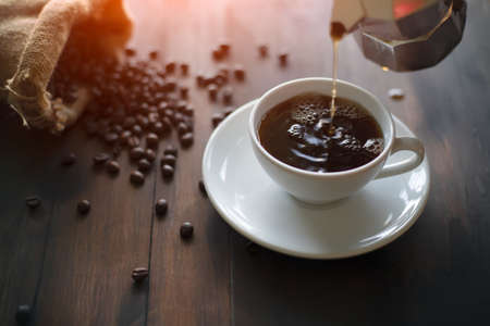 that hand is Pouring coffee from the Italian coffee maker(mocha pot) into a white ceramic coffee cup Placed on a brown wood table there are roasted coffee beans, sag in the morning