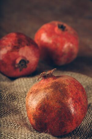 styled: Styled shot of pomegranate on burlap background