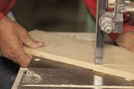 Carpenter sawing wood board on bandsaw