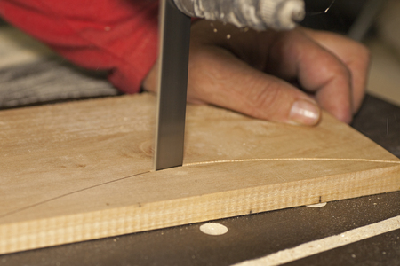 cabinet maker: Carpenter sawing wood plank on bandsaw