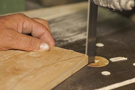 sawing: Carpenter sawing on bandsaw