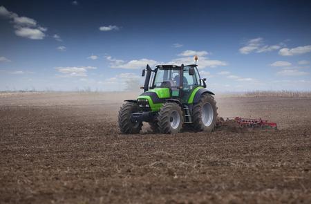 siembra: Joven agricultor en tractor de preparación de la tierra para la siembra