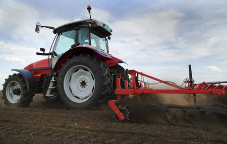 ploughing: Close-up of agriculture red tractor cultivating field over blue sky