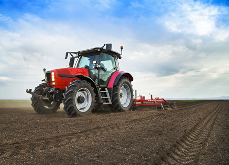 farm equipment: Farmer in tractor preparing land for sowing