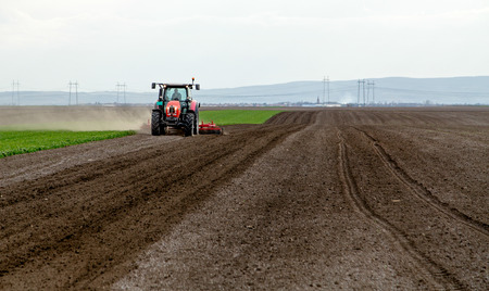 plough land: Farmer in tractor preparing land for sowing