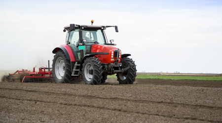 ploughing: Preparing land for sowing at spring, farmer in tractor