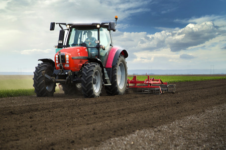 Close-up of griculture red tractor cultivating field over blue sky