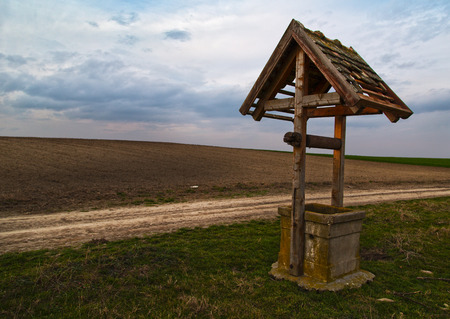 draw well: An old well near rural road at field. Stock Photo