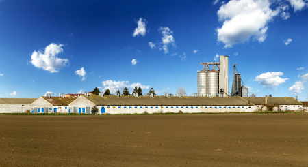 Grain silo and pig farm buildings over blue sky.