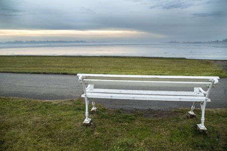 winters: White bench at lake on winters day.