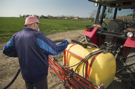 sprayer: Farmer pouring water into tractor sprayer at field