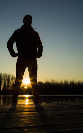 powerfull: Silhouette of young woman at sunset on lake looking at camera with powerfull, strong attitude