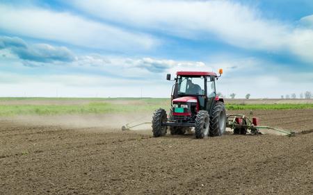 Giovane agricoltore semina in campo con seminatrice pneumatica