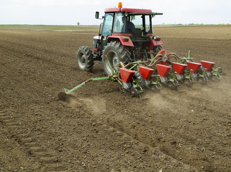 sowing: Young farmer sowing crops at field with pneumatic sowing machine