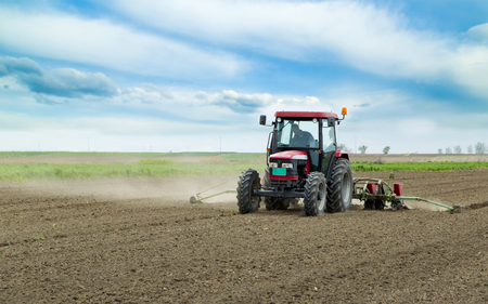 seed drill: Young farmer sowing crops at field with pneumatic sowing machine