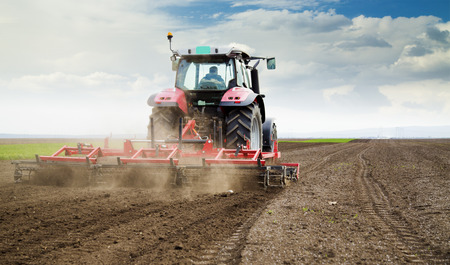 agriculture machinery: Farmer in tractor preparing land for sowing