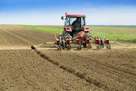 siembra: Joven agricultor siembra de los cultivos en el campo con máquina sembradora neumática Foto de archivo