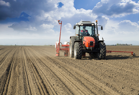 seed drill: Farmer in tractor sowing crops at field with seed scattering agricultural machine
