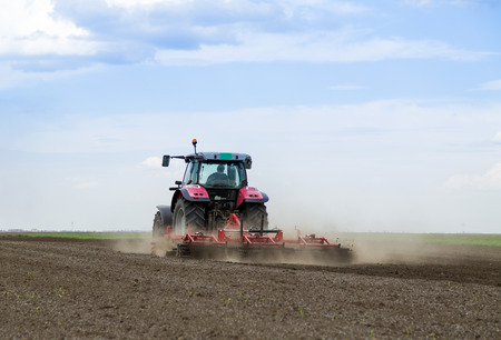 plough land: Red tractor driven by farmer cultivating land at spring