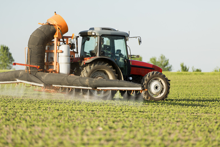 Tractor spraying soybean crops field with sprayer, pesticides and herbicides