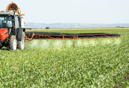 Farmer in red tractor spraying soybean field with herbicides, pesticides and fungicides