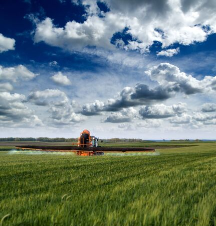 farm equipment: Spraying crops field Stock Photo