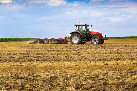 ploughing: Tractor cultivating wheat stubble field, crop residue. Stock Photo