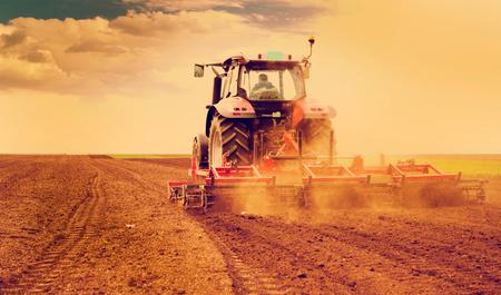 Rolnik w ciągniku przygotowanie gruntu do siewu