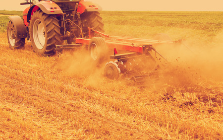 residue: Tractor cultivating wheat stubble field, crop residue. Photo manipulated to achieve old cross processing xpro look.