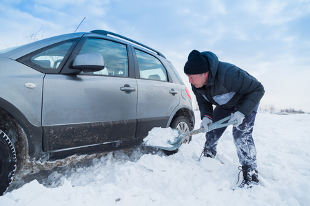 Man shoveling snow to free his stuck car Imagens